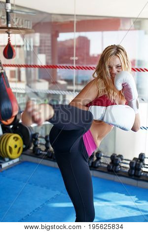 Young martial artist woman kicking in gym into camera exercise