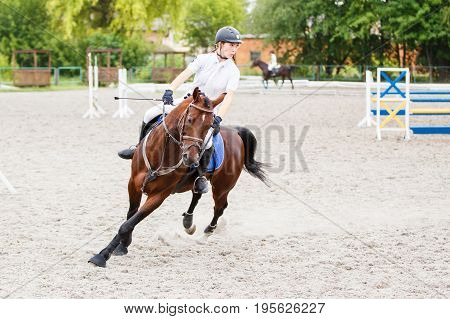 Young rider girl on bay horse galloping on her course at show jumping competition