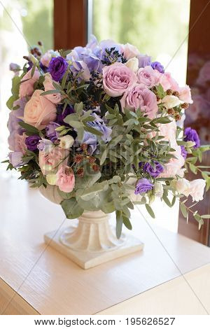 Tender decoration with the violet, blue, pink flowers and greenery for the wedding ceremony