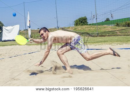 Young Adult Man Plays Tennis On The Beach