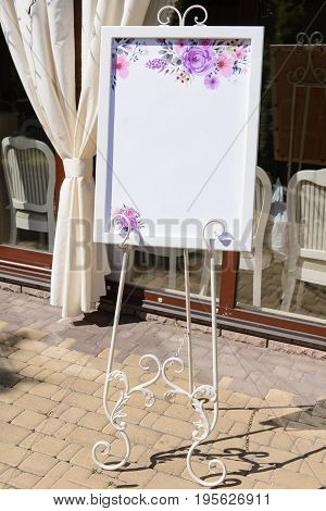 Wedding board on the white forged stand with a guest list near the restaurant