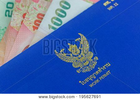 BANGKOK, THAILAND - MAY 2017: Closeup of golden Garuda on front cover of Blue Thai Work Permit book (WP.11) above Thai Baht banknote money in Bangkok, Thailand on May 14, 2014