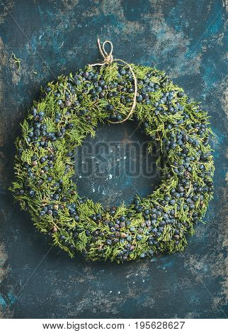 Christmas decorative green wreath with fresh blueberries and natural herbs over dark blue shabby plywood wall background, vertical composition