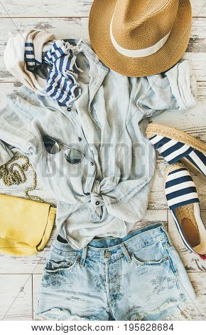 Summer outfit flatlay. Pastel coloured summer women's clothing, parquet background, top view. Blue shorts, linen shirt, straw hat, yellow bag, sunglasses, striped neckerchief, espadrillas