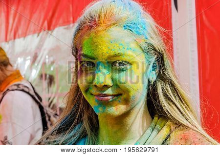 Moscow, Russia - June 3, 2017: Portrait of a beautiful gray-eyed teenage girl blonde with a face stained with paint on the Holi holiday. Light green, yellow and blue vibrant splashes of powder paint