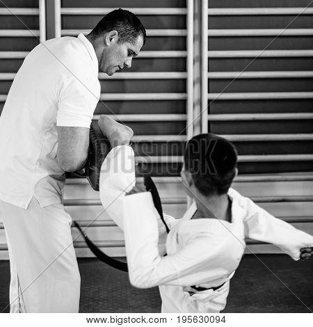 Taekwondo instructor working with boy on training indoors black and white image