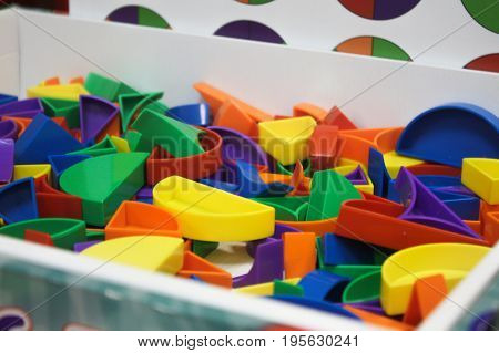 Bricks for kids in a box. Abstract objects, mosaic, puzzle for the development of mental abilities, logical thinking. Board games for children in game room, playroom