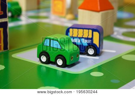 Kids toy cars. The colored wooden cubes for children on the table. The colored blocks of wood on the table. Abstract objects, mosaic, puzzle for the development of mental abilities, logical thinking. Board games for children in playroom