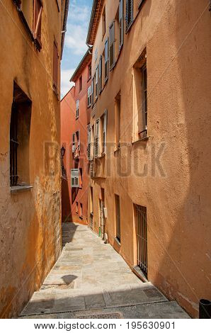 View of narrow alley and buildings with shops in the city center of Grasse, known for producing perfumes. Located in the Alpes-Maritimes department, Provence region, southeastern France