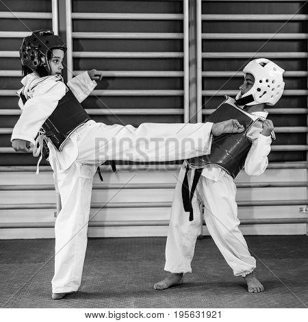 Taekwondo kids sparring on training indoors black and white image