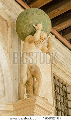 Small Renaissance statue of the mythological character Atlas carrying the world on his shoulders. Exterior of the historic Doge's Palace Venice.