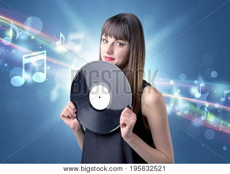 Young lady holding vinyl record on a blue background with musical notes behind her