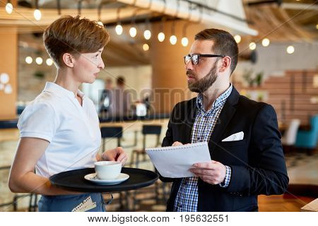 Helpful servant with tray talking to one of customers in restaurant