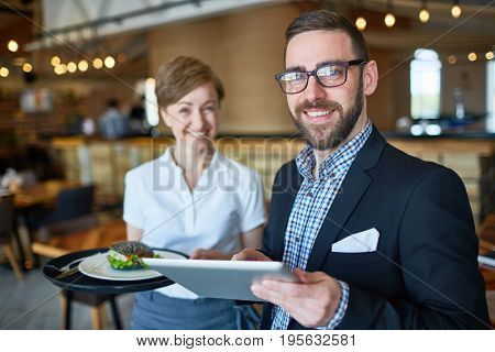 Elegant trader with touchpad and waitress with sandwich on tray