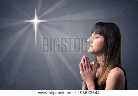 Young woman praying on a grey background with a shiny cross silhouette above her