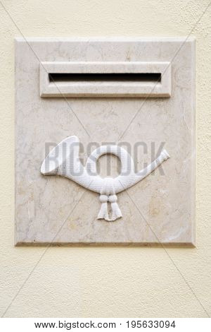 Marble stone mailbox isolated in a rough yellow wall