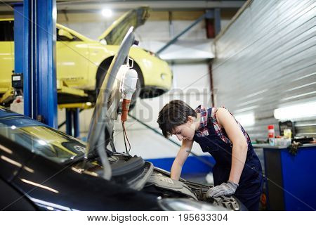 Female mechanic tuning one of cars in garage