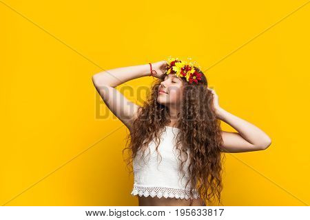 Brunette curly haired girl wearing flower chaplet touching head standing with closed eyes.
