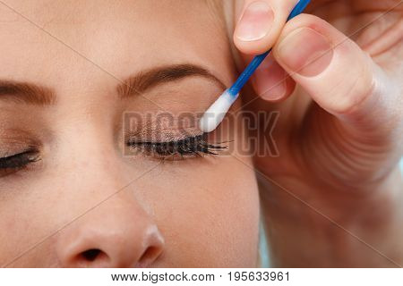 Visage beauty concept. Closeup portrait of woman face getting her eye makeup done with cotton buds
