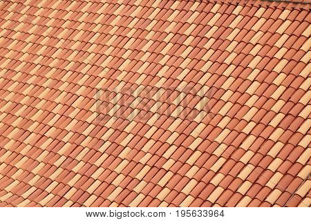 Rooftiles laid uniformly with regular patterns of yellow and orange colored tiles