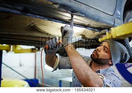 Mechanic with lamp overhauling low panel of car