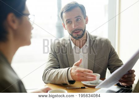 Confident agent explaining main points of financial contract to client