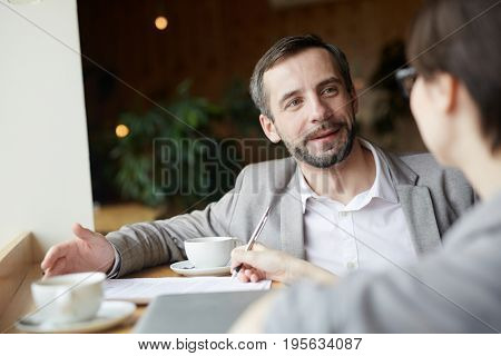 Employer having talk with applicant in cafe