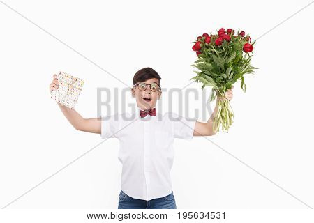 Cheerful little boy holding present box and bouquet of tulips posing excitedly on white background.