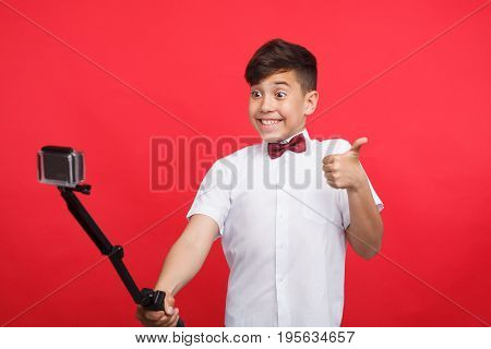 Little cheerful boy in shirt taking selfie with monopod showing thumb up on red background.