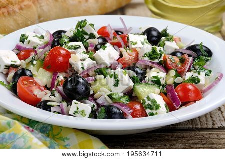 greek salad orzo pasta with black olive red onion and cucumber cherry tomatoes feta and herbs. Horizontal shot. foreground