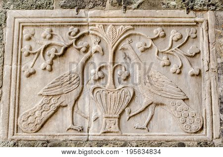 Historic stone plaque with a carving of two peacocks facing a flowering plant exterior wall of the Basilica di San Marco in Venice Italy.