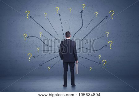 Businessman standing in front lines and question mark signs concept on background