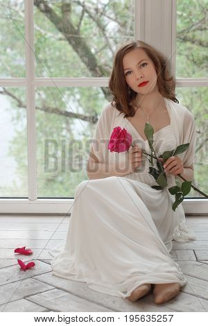 A beautiful girl in a white dress is sitting on the floor with her back to the window. She took off her shoes and held a beautiful rose flower in her hands.