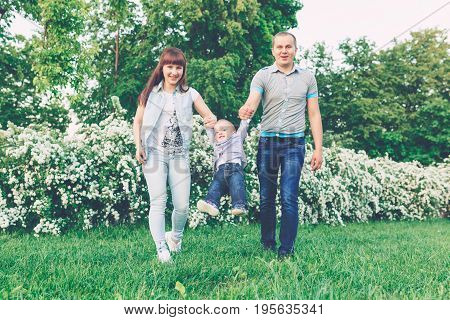 Happy joyful young family father mother and little son having fun outdoors playing together in summer park. Mom Dad and kid laughing and hugging enjoying nature outside. Sunny day good mood