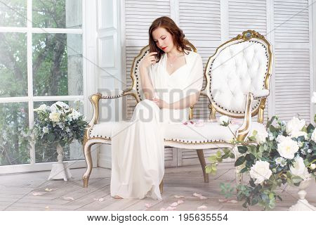 A girl in a white dress is sitting on a beautiful sofa in a room filled with light from the window.