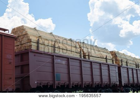 Full rail cars of timber against the sky