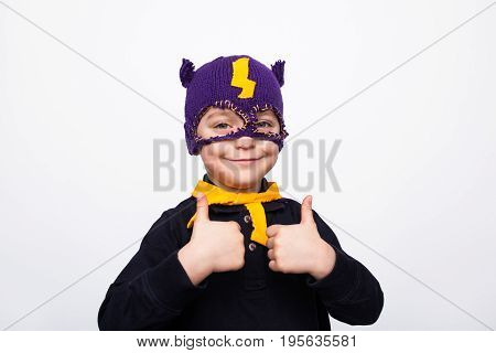 Cheerful content kid in superhero mask holding thumbs up on white background
