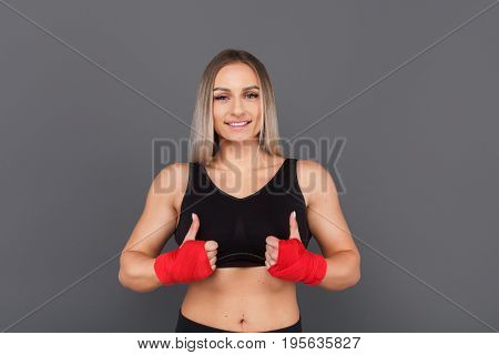 Adult woman in sportswear and red boxing band holding thumbs up and looking at camera on gray.