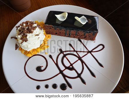 Delicious dark chocolate cake decorated with slice of white chocolate curls whipping cream and chocolate music note in white plate on wooden table.