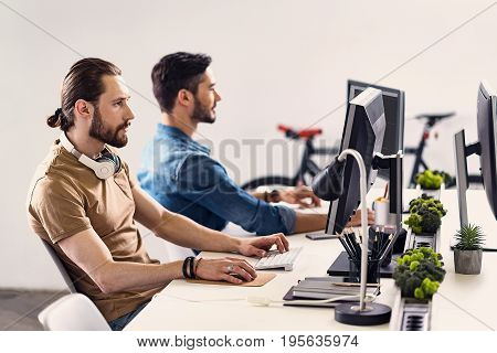 Side view male expressing seriousness while typing on keyboard at table in office. He sitting at table