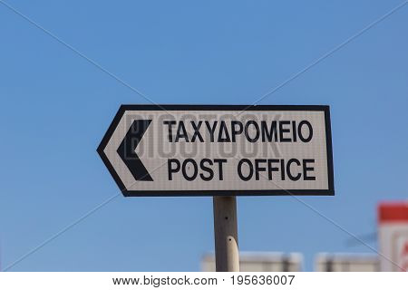 white post office sign on the road