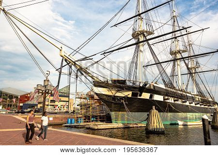 Baltimore Maryland USA - July 11 2017: Two girls walk past the USS Constellation one of the historic ships docked in Baltimore's Inner Harbor. Built in 1854 this ship was the U.S. Navy's last sail-only warship.