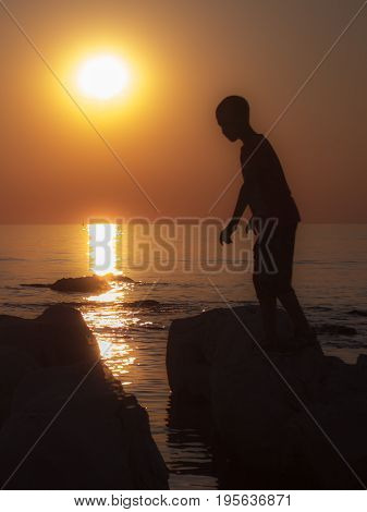 An indigenous boy on the sea shore illuminated by the setting sun.