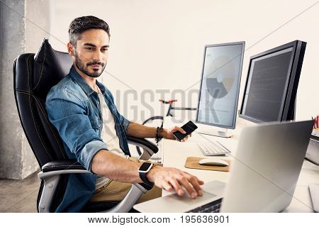 I know what to do. Portrait of serious male having job on notebook computer in monitor room