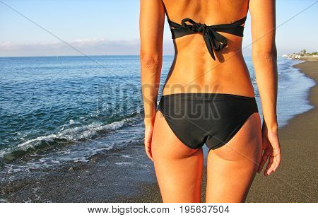 Woman on the beach. Sexy female tanned buttocks. Vacation at Paradise.