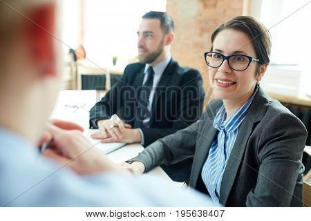 Confident employer listening to applicant at interview
