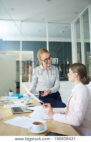 Happy girl showing and explaining data to co-worker