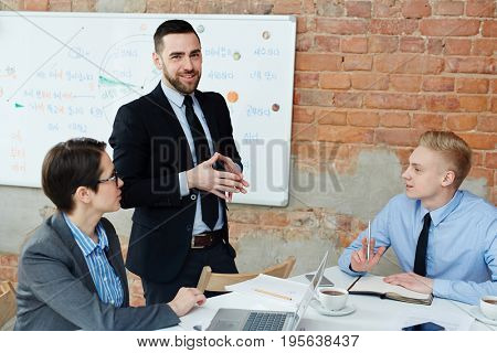 Successful employer and his team brainstorming and discussing ideas