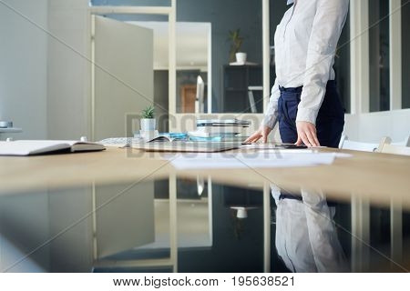 Woman in formalwear standing by her workplace in office