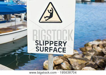 Warning: Slippery Surface sign near the sea